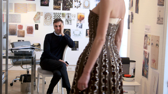 New Dior designer Raf Simons looks at a vintage Dior dress from the documentary DIOR & I, directed by Frederic Tcheng.